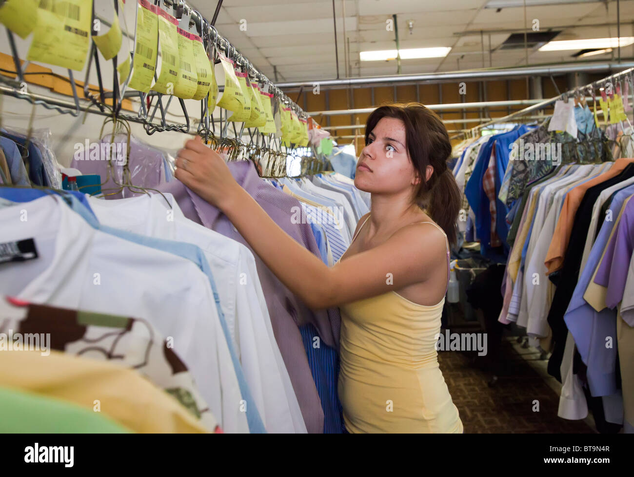 Broomfield, Colorado - Workers press and hang shirts in a shirt laundry. - Stock Image