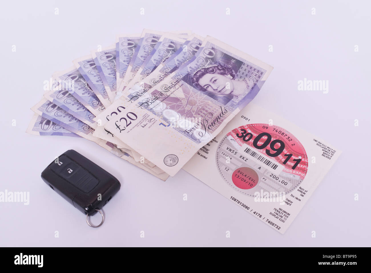 A car tax disc vehicle license with £200 in cash and car keys on a white background - Stock Image