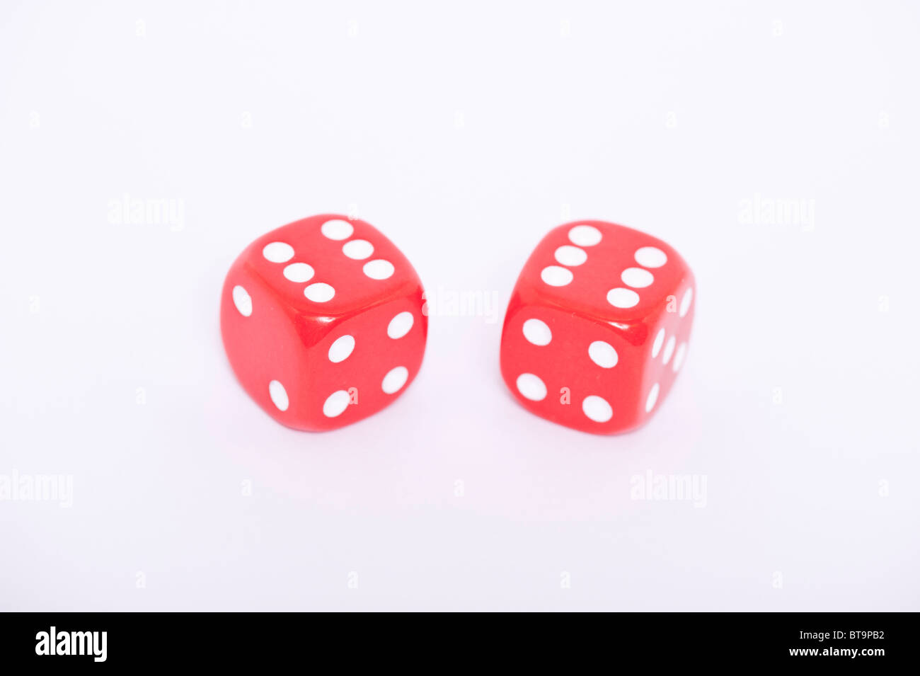 A pair of red dice both showing a six on a white background - Stock Image