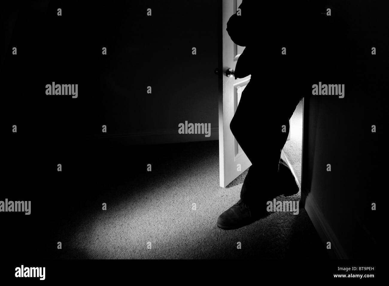 Man leaning on the wall of a dark room - Stock Image