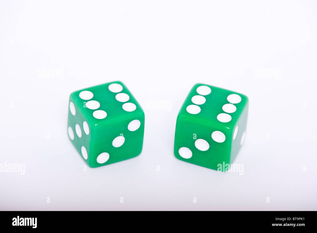 A pair of green dice both showing a six on a white background - Stock Image