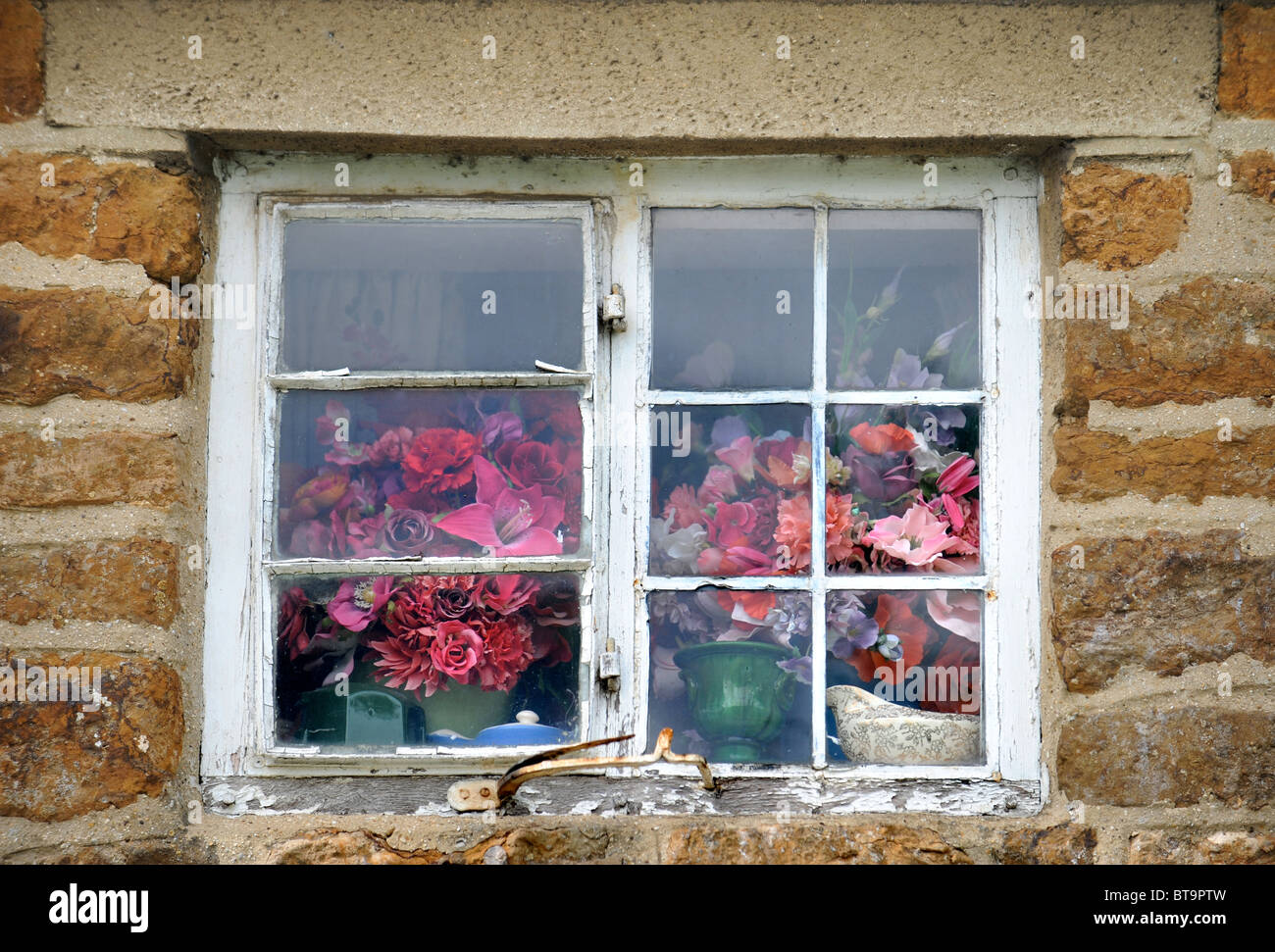Flower arrangements seen through an Oxfordshire cottage window UK - Stock Image