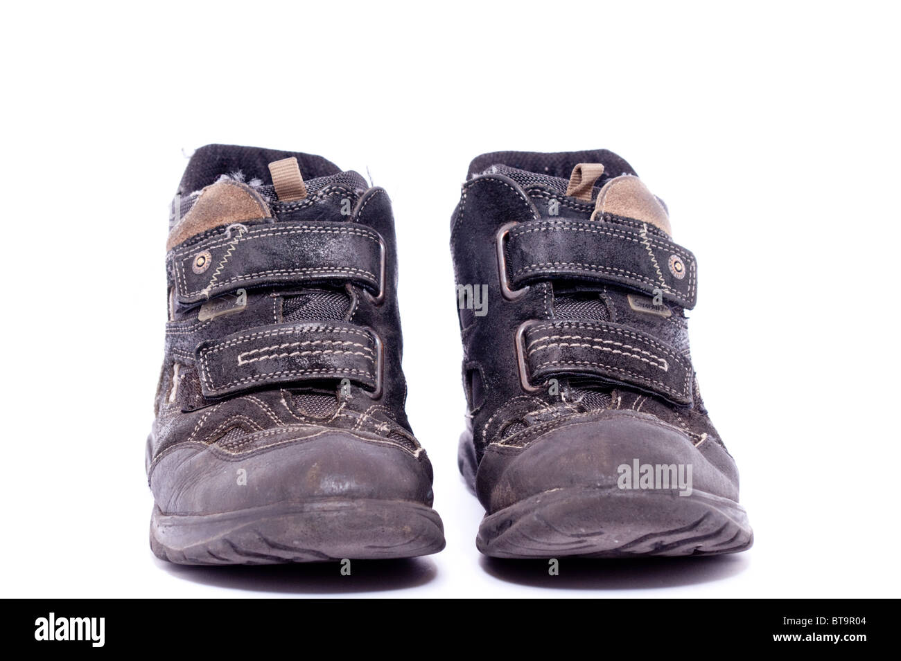 A pair of well worn boys boots on a white background - Stock Image
