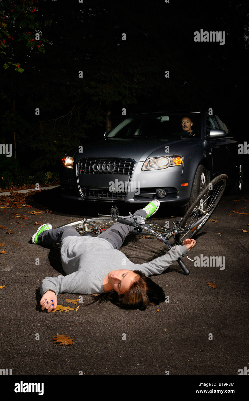 Male driver in car stopped to look at a fallen young female bicyclist on the road after an accident - Stock Image