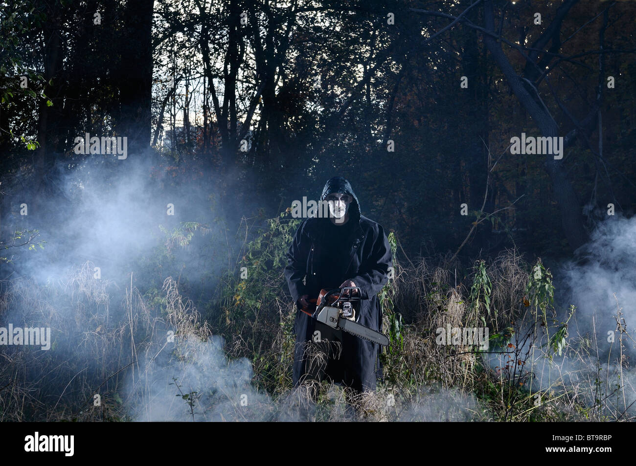Glaring pale evil man in black coat with a chainsaw in a misty forest in the Fall at Halloween - Stock Image