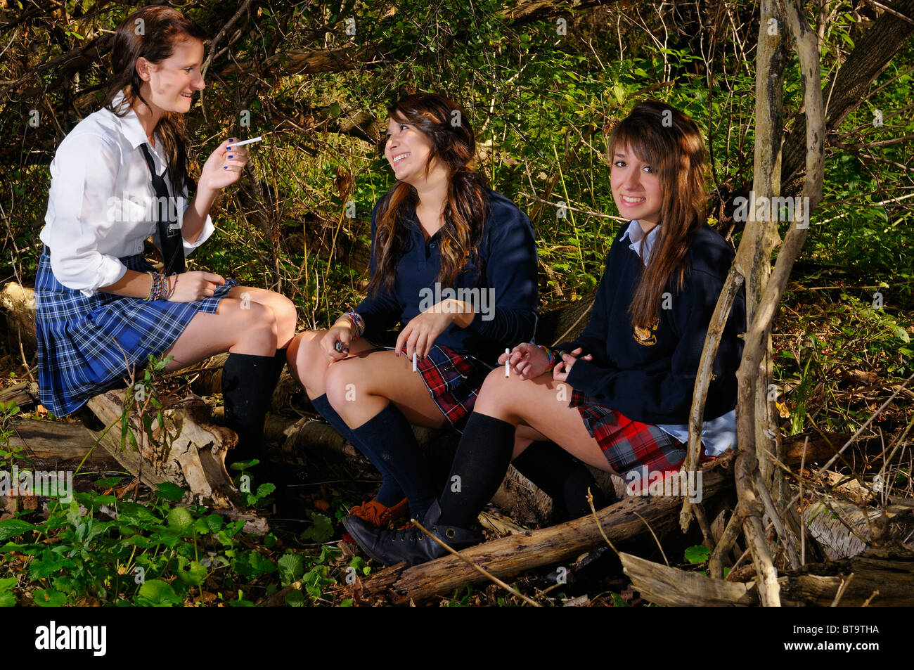 Three teenage girls private school students friends after school hiding in a forest to smoke cigarettes - Stock Image