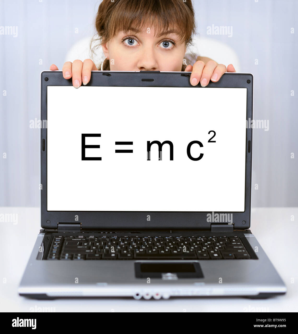 Young woman shows us a computer screen with formula - Stock Image