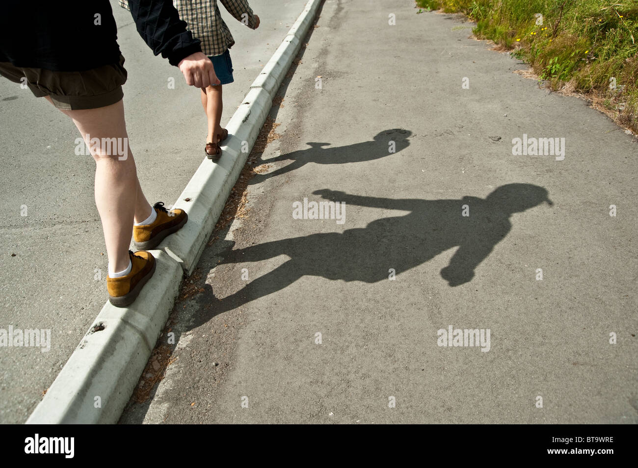 Shadows of a mother and her son walking tiptoeing - Stock Image
