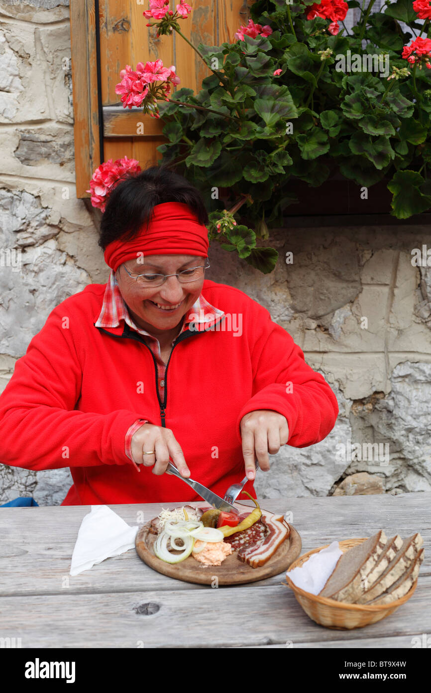 Woman with peasant snack, hearty snack in front of the Koschutahaus mountain lodge, Karawanken, Carinthia, Austria, - Stock Image
