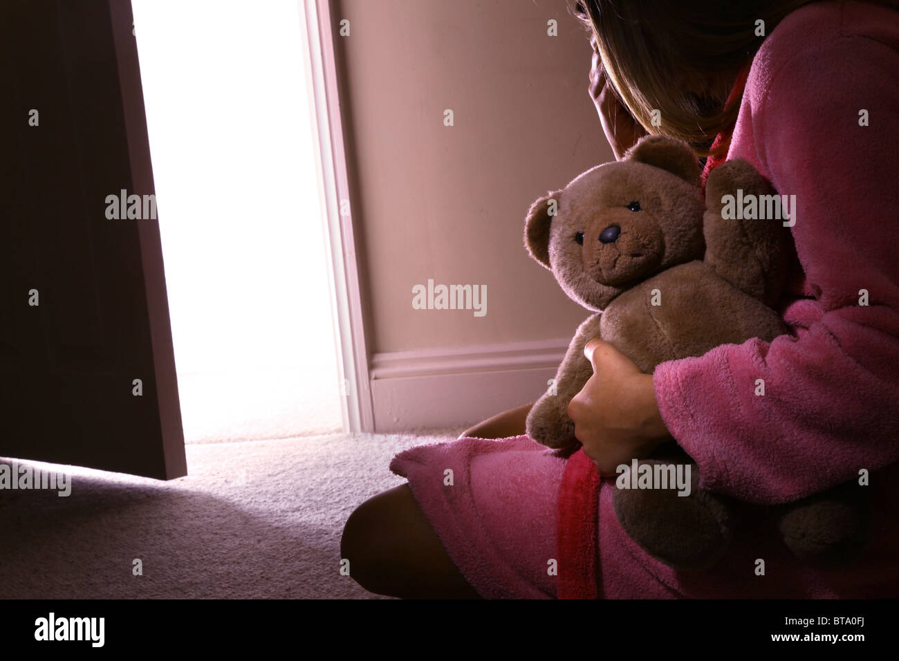 Young girl sitting holding a teddy bear, back view. - Stock Image