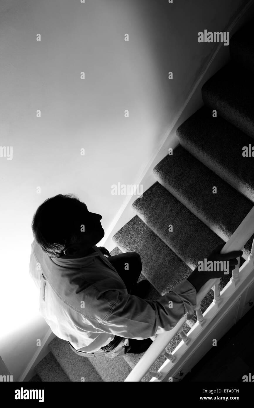 Man walking upstairs, heavy shadows.  Black & white - Stock Image
