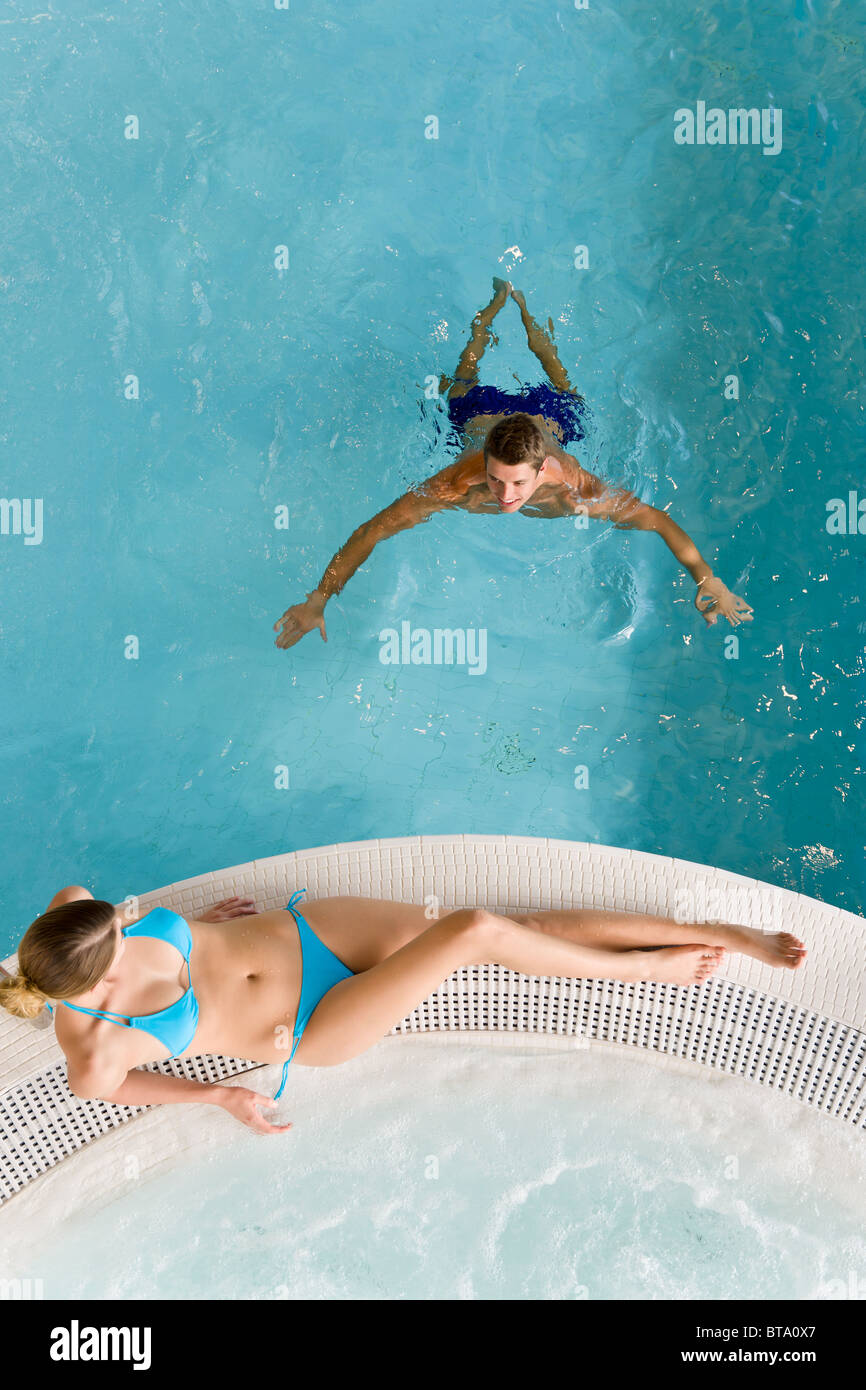 Top view - young couple relax in swimming pool sitting at bubble bath - Stock Image