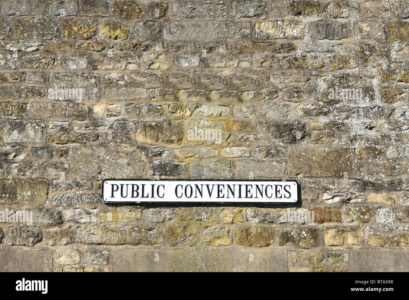 Public Conveniences - sign indication the location of toilets, UK. Old stone wall background. - Stock Image