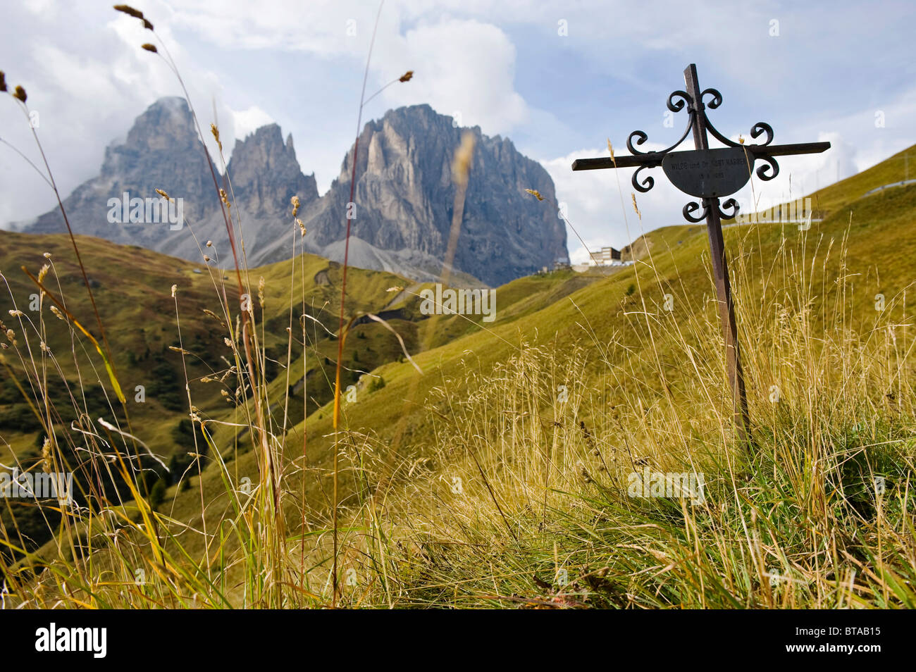 Cross as a memorial to people killed in a traffic accident on a mountain road, in front of Langkofel and Plattkofel - Stock Image