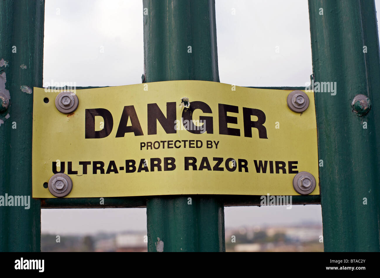 Industrial site protected by ultra-barb razor wire - Stock Image