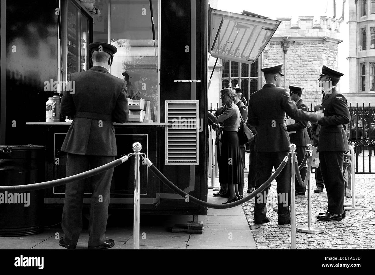 Black and White English soldiers in uniform buying at a kiosk next to Westminster church - Stock Image