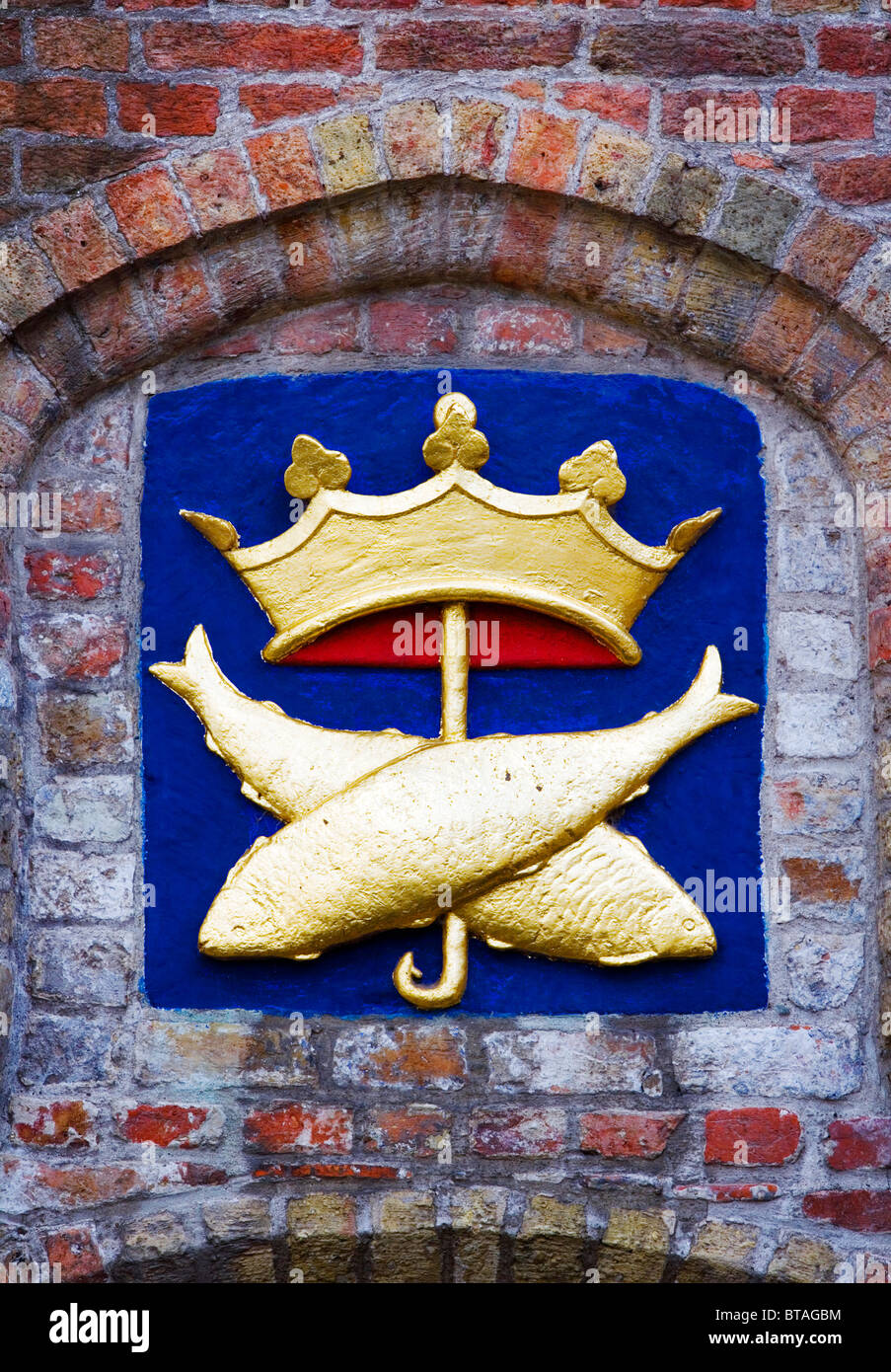 Historic gold sign, crown, fish-hook & crossed fish, Bruges, Belgium, Europe - Stock Image