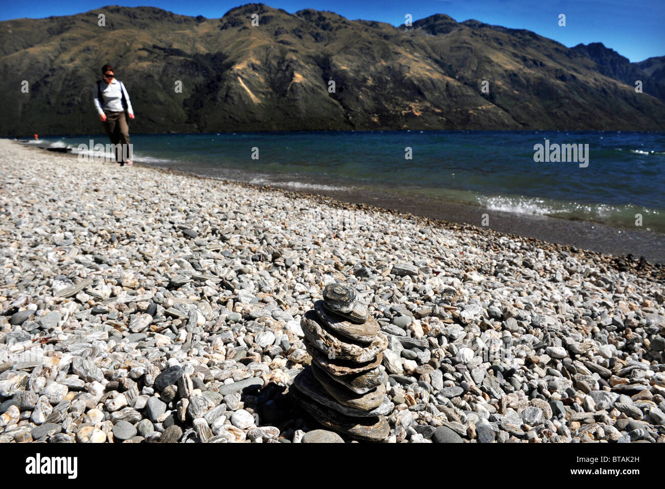 Woman walks on the stony beach of Lake Wakatipu, near Queenstown, New Zealand. The lake has views of nearby mountains. Stock Photo