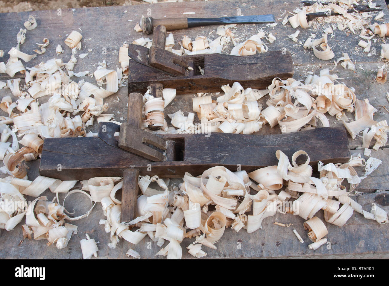 primitive carpentry tools along with wood shavings sit on a table in rural Yunnan province, China - Stock Image