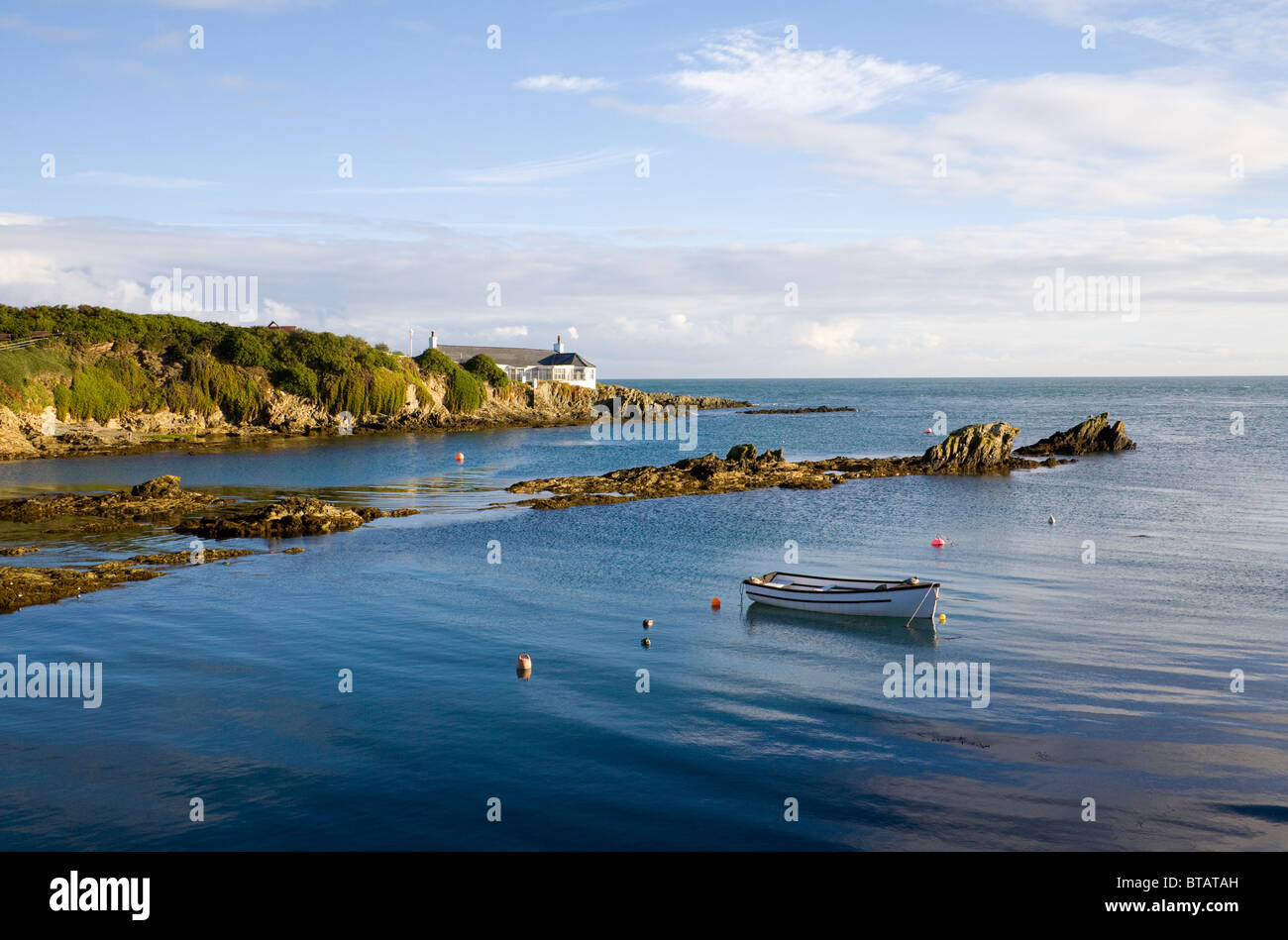 Bull Bay Isle of Anglesey North Wales October on a still autumn day with a white rowing boat moored and white cottage - Stock Image