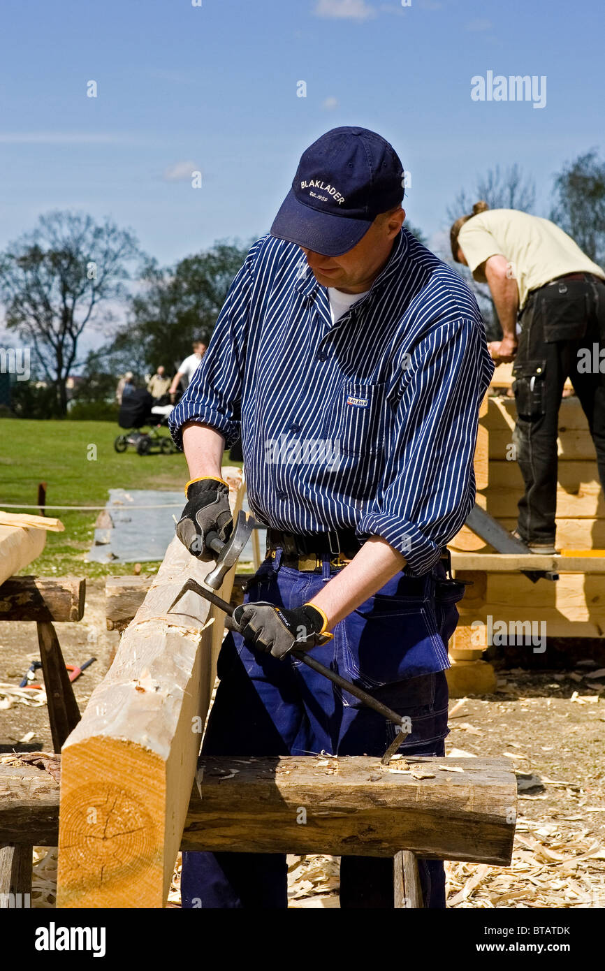 Carpenter at work (Sweden) preparing logs for a cabin in early spring - Stock Image