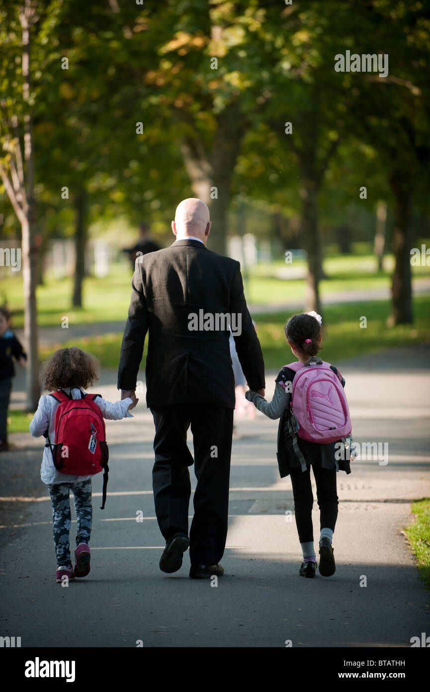 Rear view of a father walking hand in hand with his two small daughters on their way home from primary school, UK - Stock Image