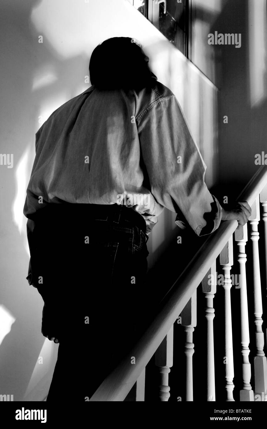 Man walking upstairs back view. Black & white - Stock Image