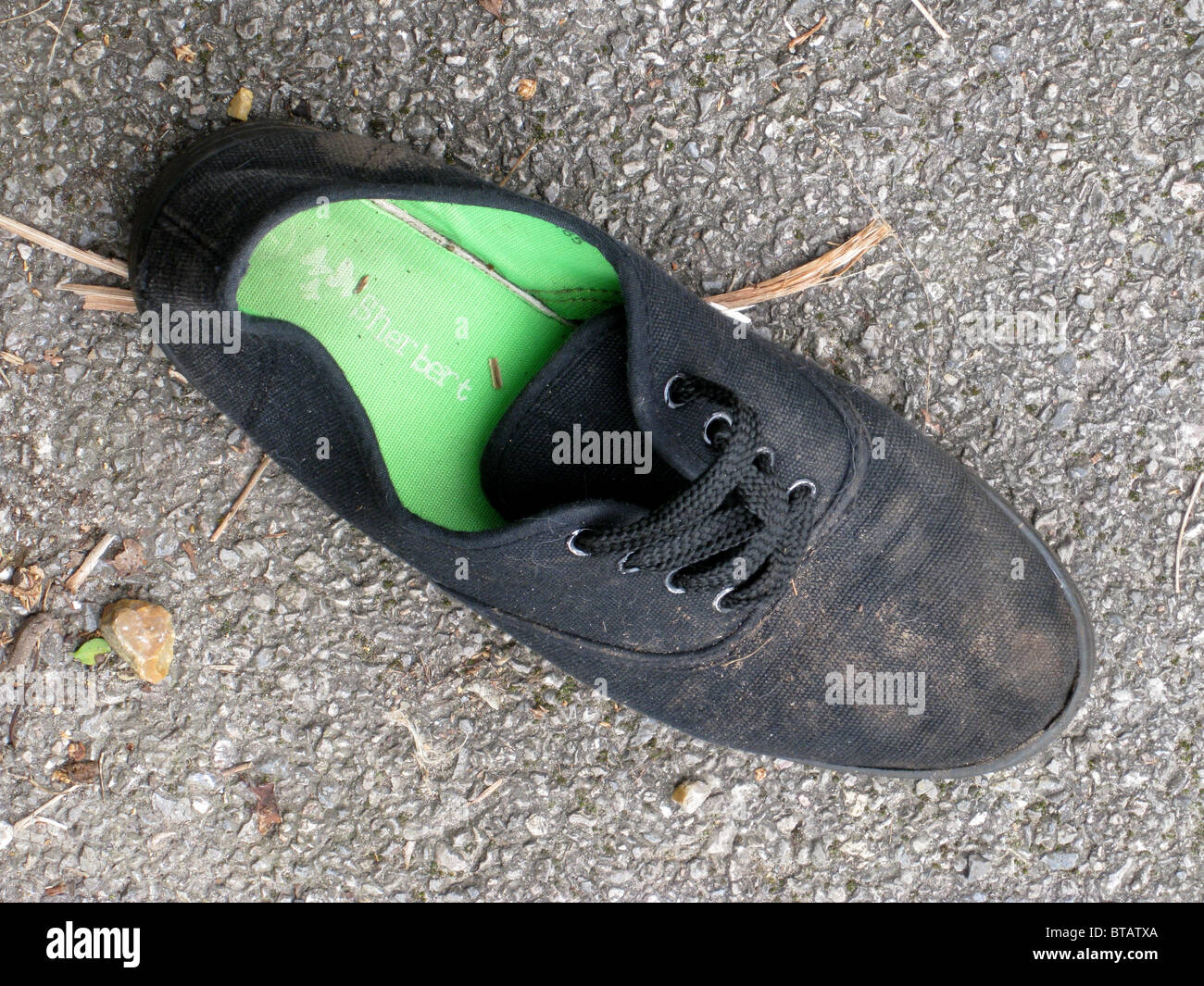 Discarded Black Plimsoll on Pavement - Stock Image