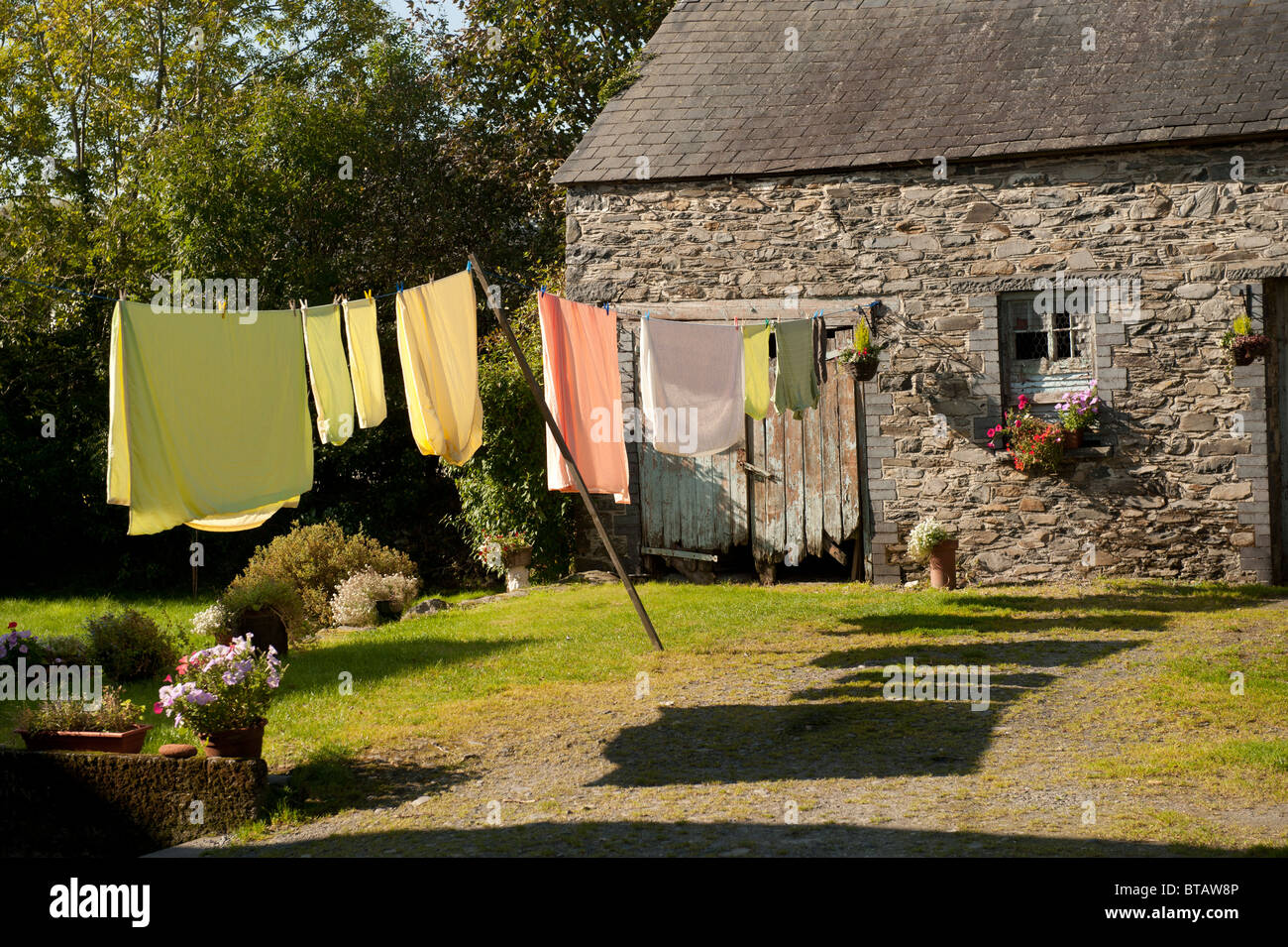 Clothes hanging out to dry on a washing line in a rural cottage garden, UK - Stock Image
