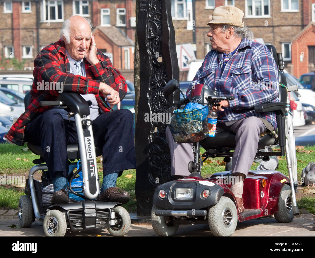 Two Elderly Men on Motability Scooters - Stock Image
