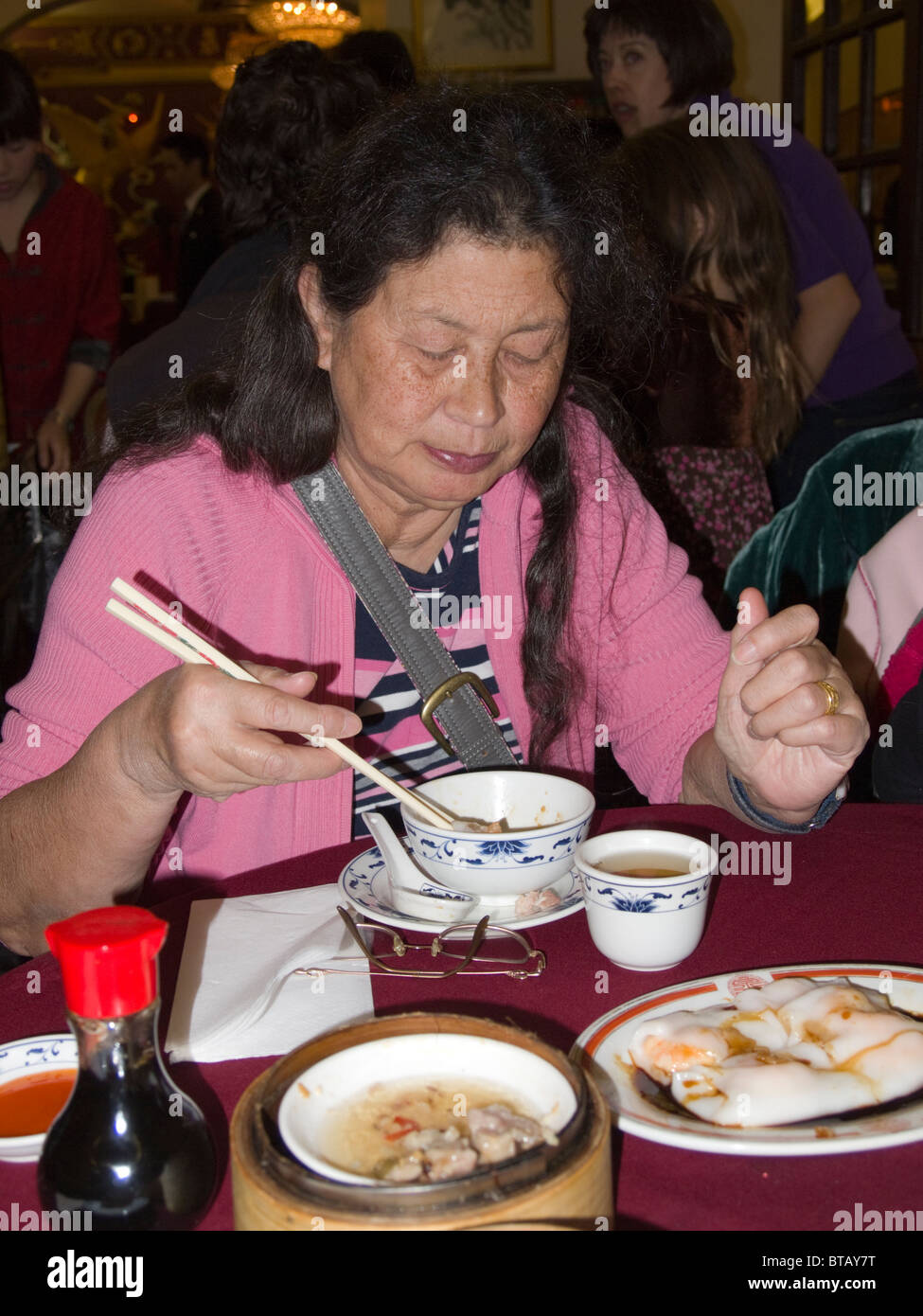 Woman eating dim sum in a Chinese restaurant, Chinatown, London, England, UK - Stock Image