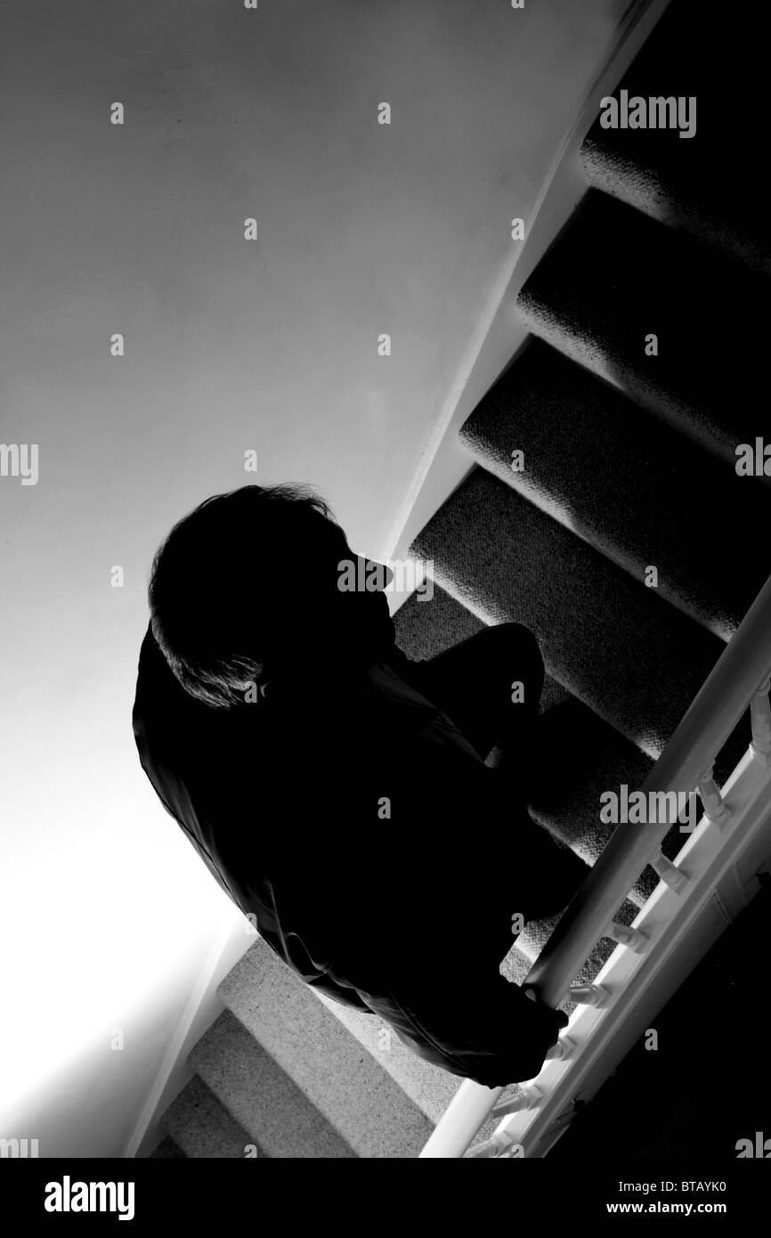 Silhouette of a man walking up a dark stairway - Stock Image