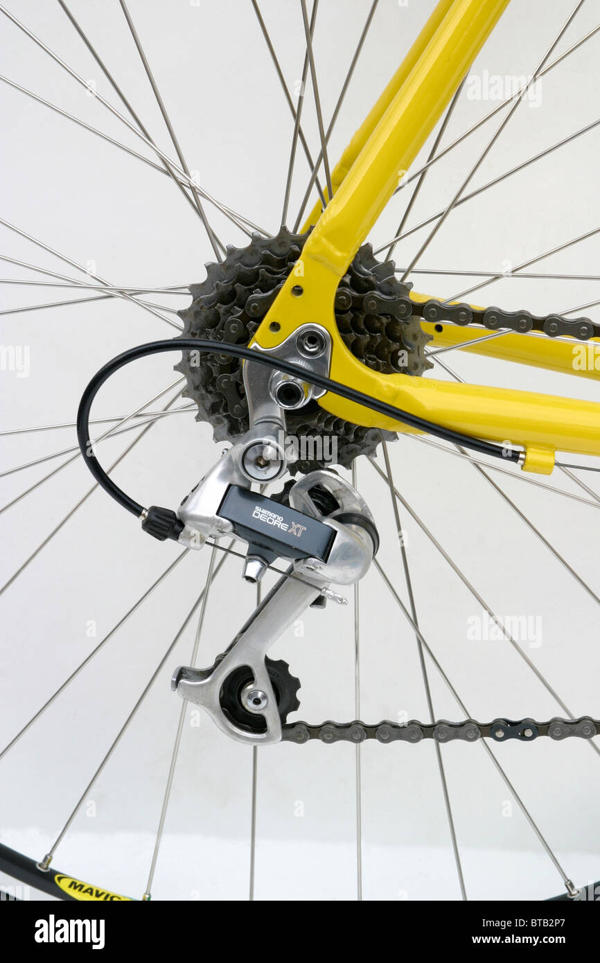 cutout of closeup of Shimano derailleur gear yellow hybrid roadster trekking fitness training style bike with 700c - Stock Image