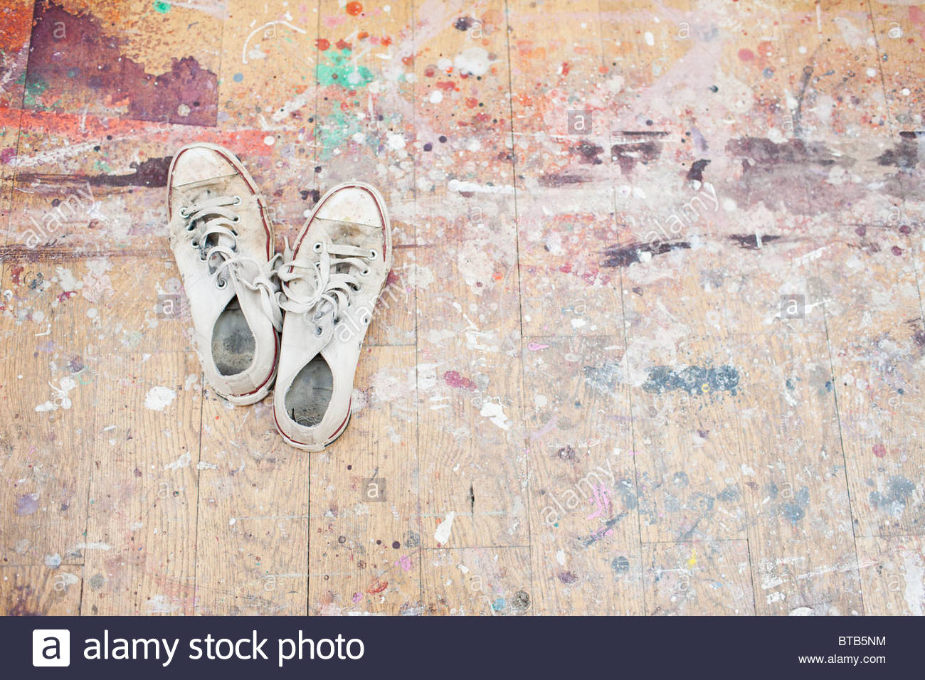 Sneakers on paint-spattered wood floor - Stock Image