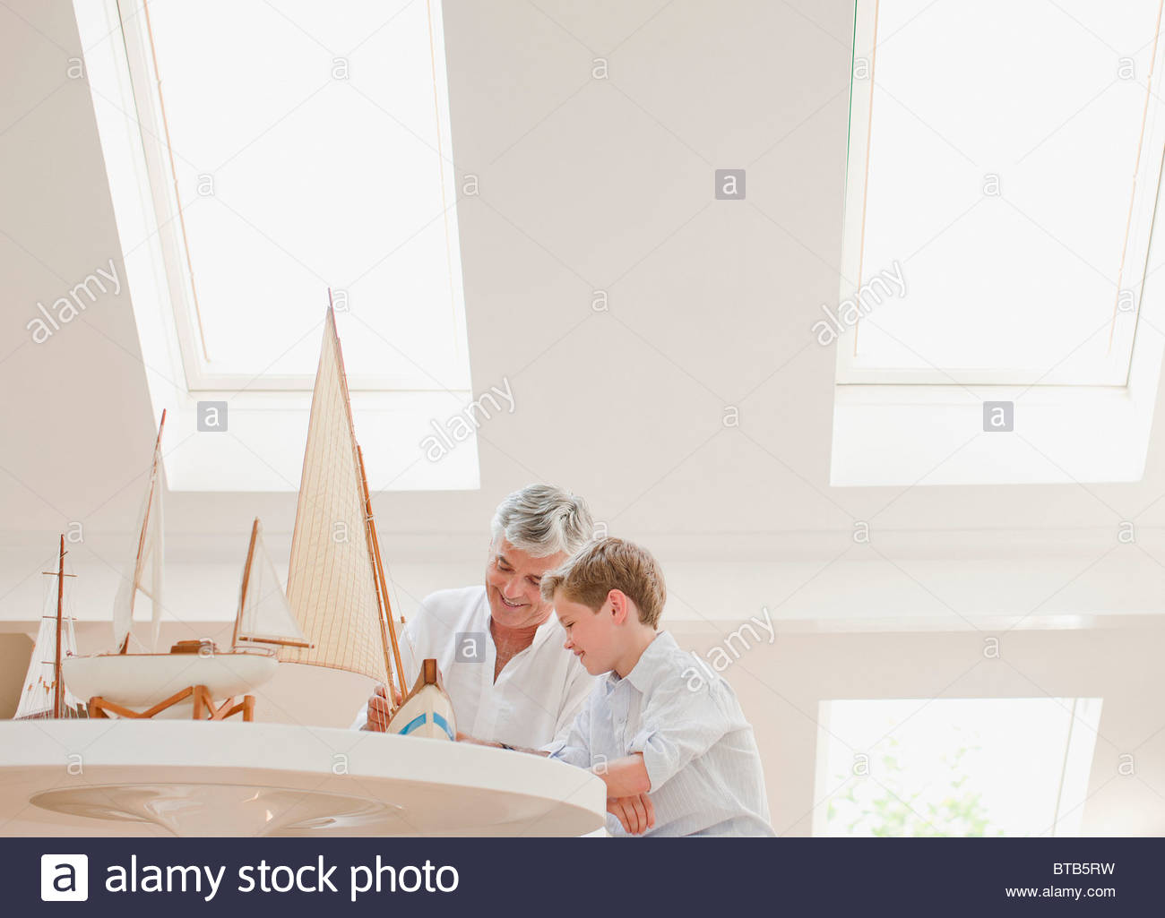 Father and son assembling model sailboat - Stock Image