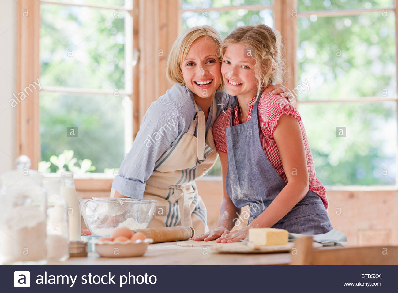 Smiling mother and daughter hugging and baking in kitchen - Stock Image