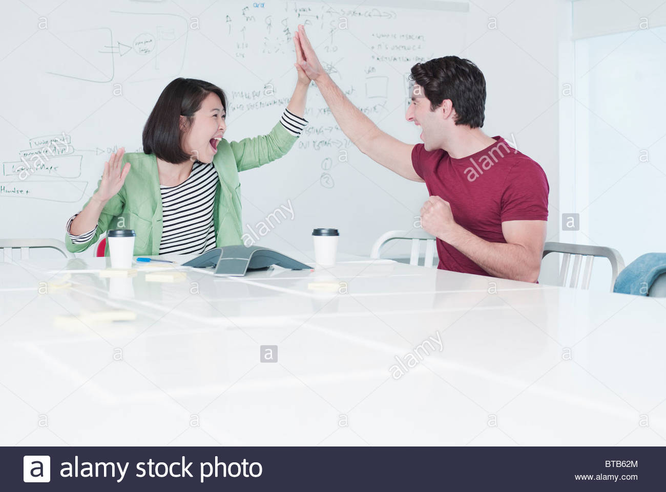Excited business people giving high five in conference room - Stock Image