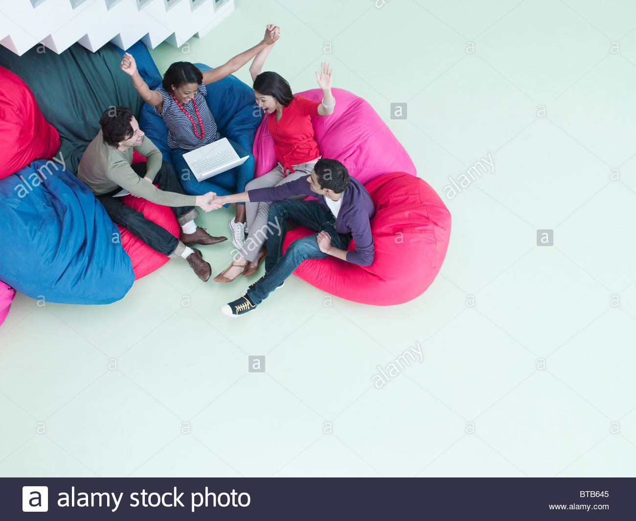 Excited business people with arms raised sitting in bean bag chairs and looking at laptop - Stock Image