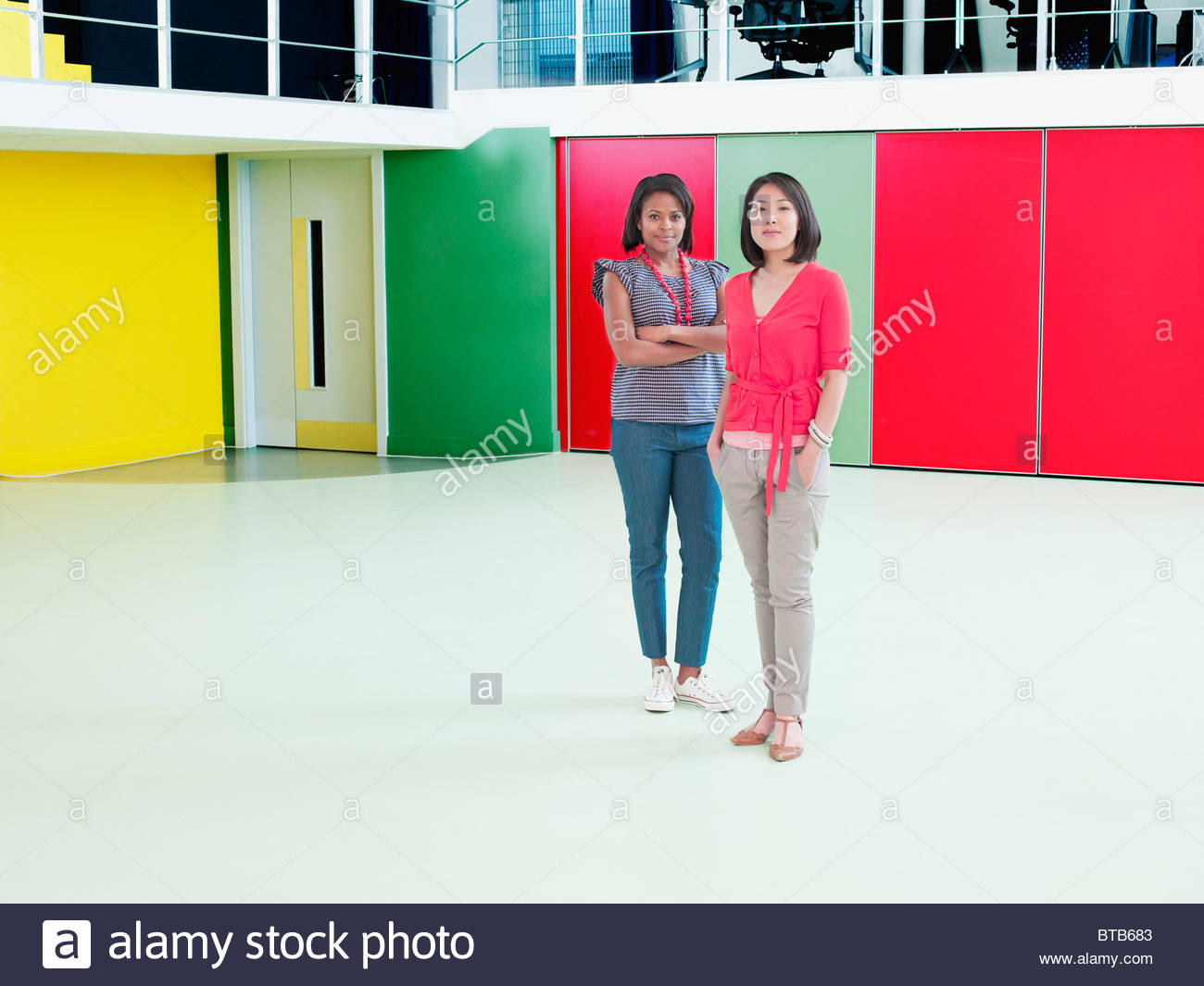 Smiling businesswomen in empty office - Stock Image