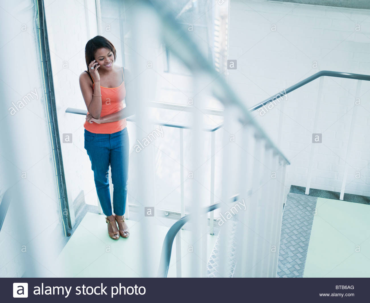Smiling woman talking on cell phone in stairway - Stock Image
