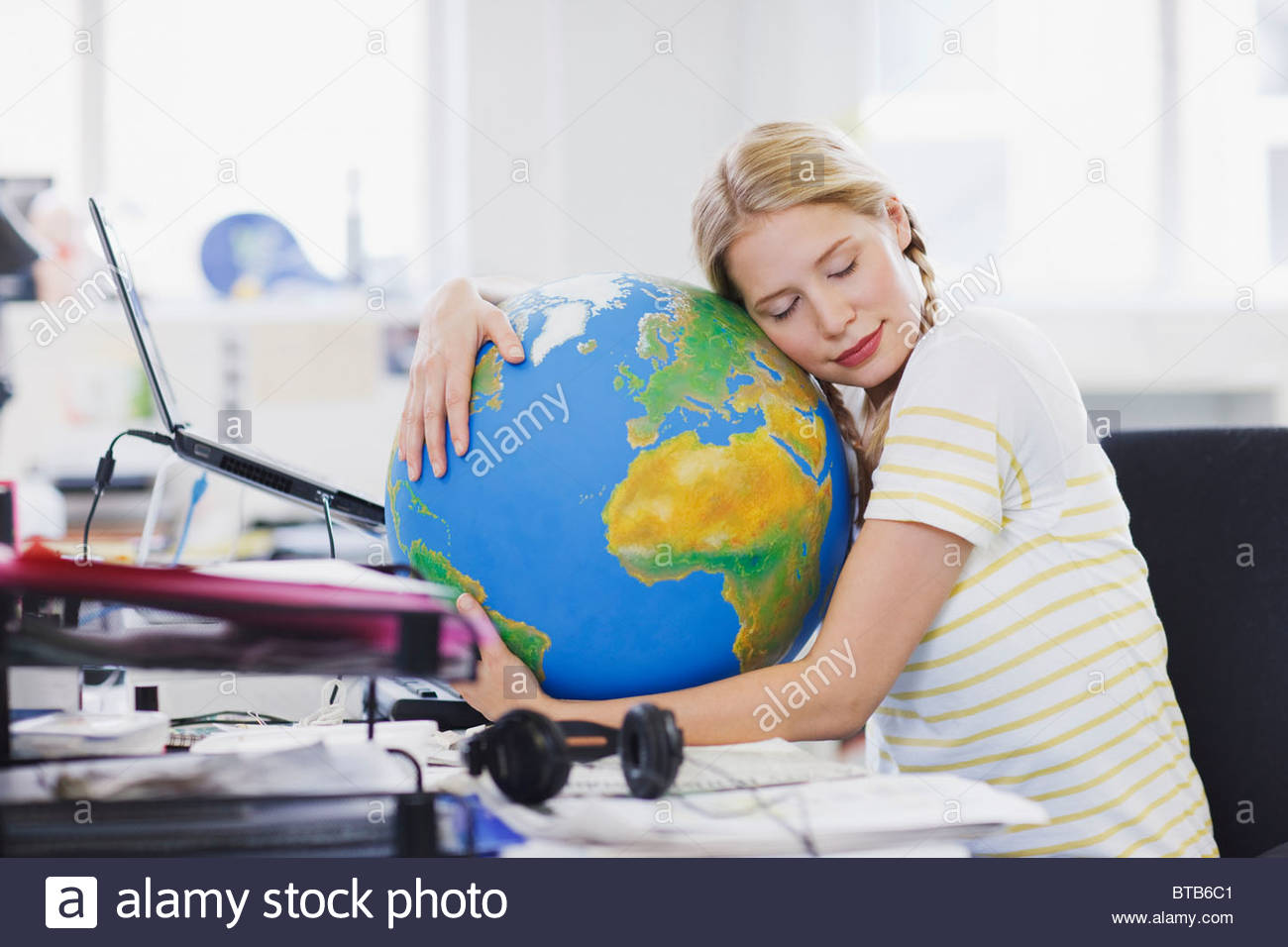 Businesswoman with eyes closed hugging globe at desk in office - Stock Image
