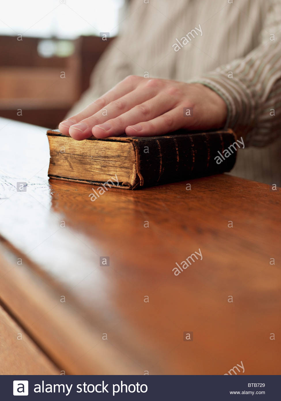 Hand of witness on Bible in courtroom - Stock Image
