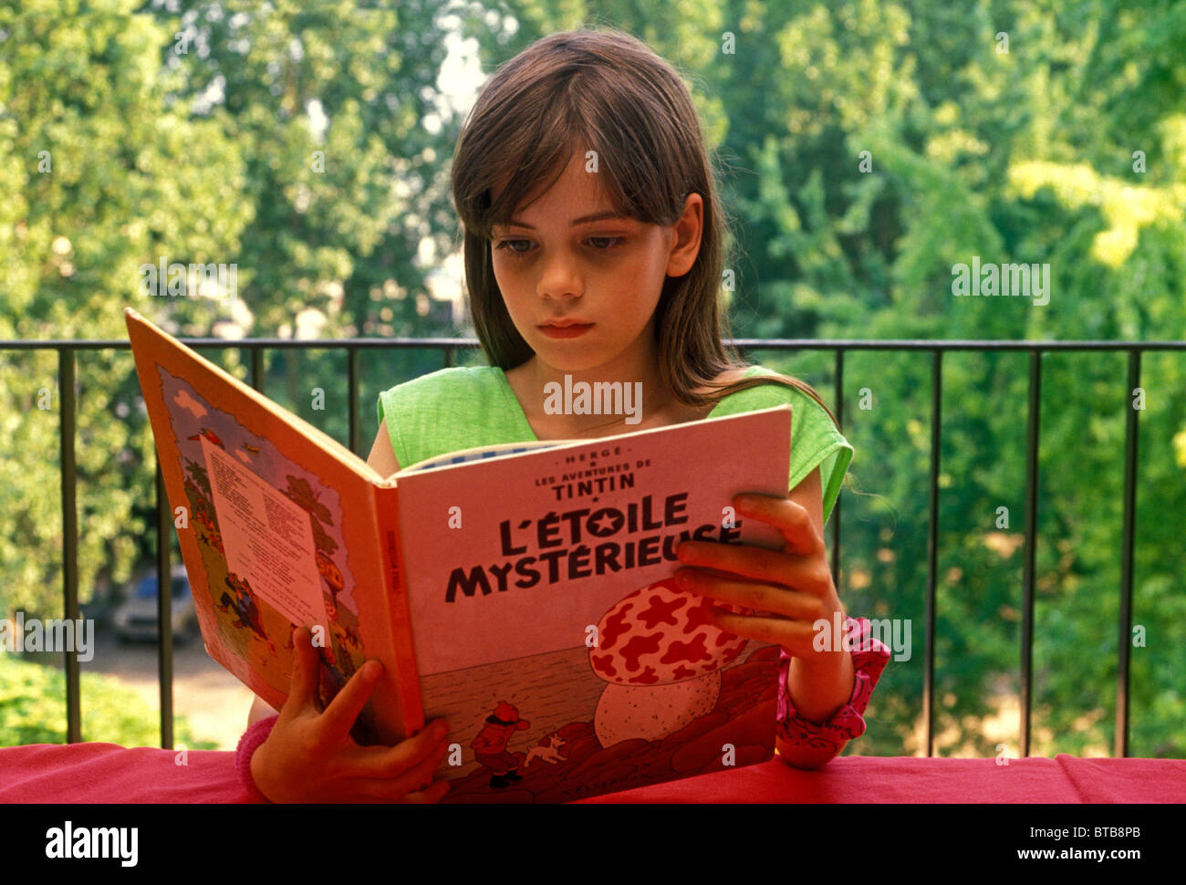 French girl, reading book, Tintin, L'Etoile Mysterieue, Herge, Verneuil-sur-Seine, Ile-de-France, France, Europe - Stock Image