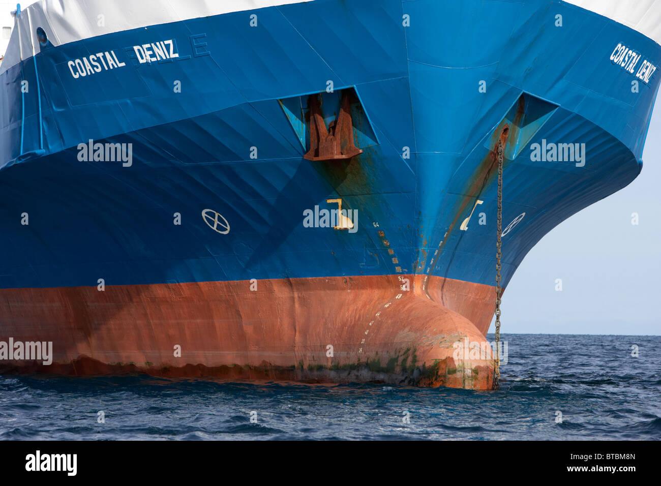bulbous bow and anchors coastal deniz dry cargo hazard a major ship at anchor in coastal waters of the uk - Stock Image