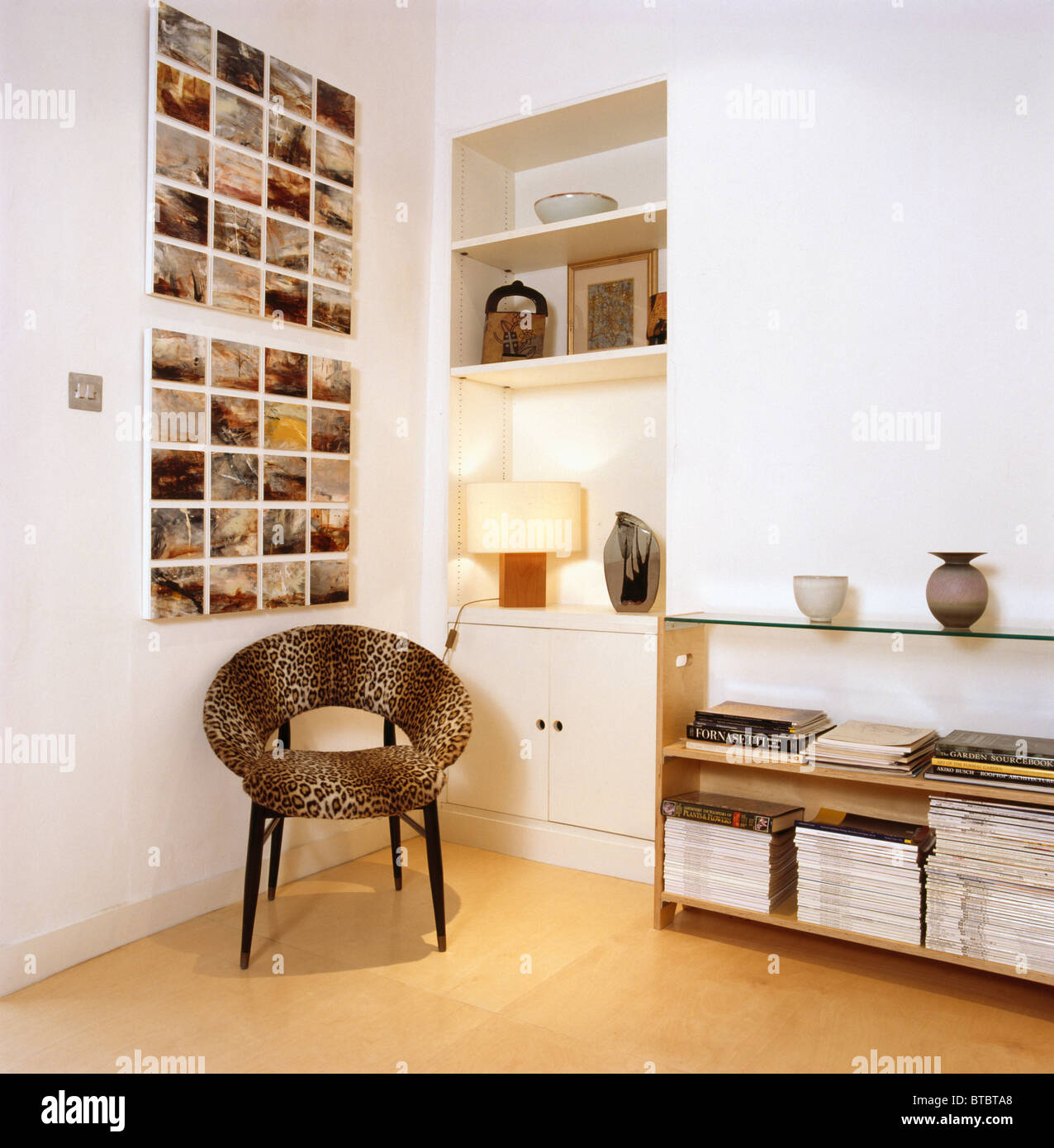 Animal-print chair below group of small photographs on wall ...