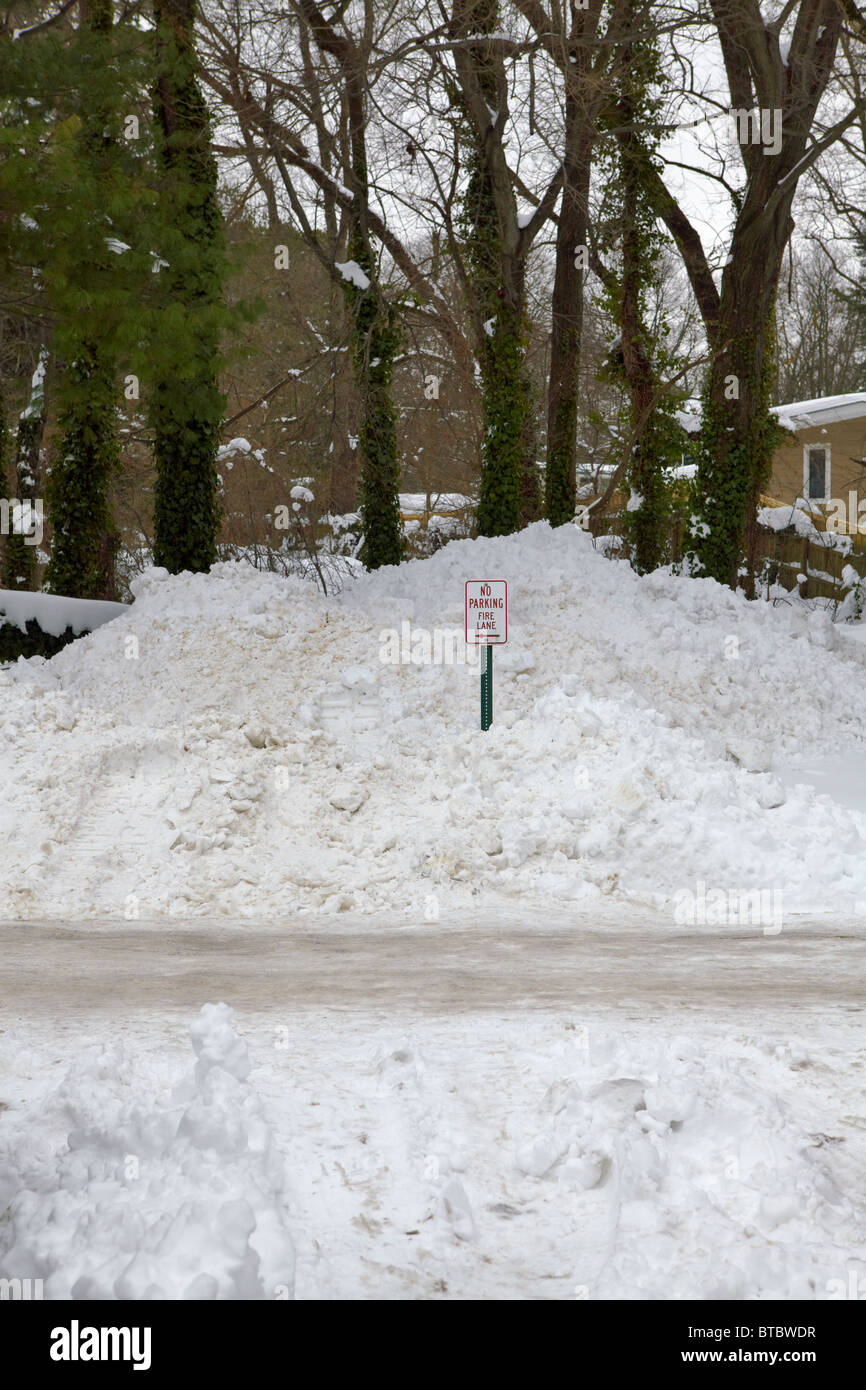 A No Parking Fire Lane sign buried in removed snow. - Stock Image