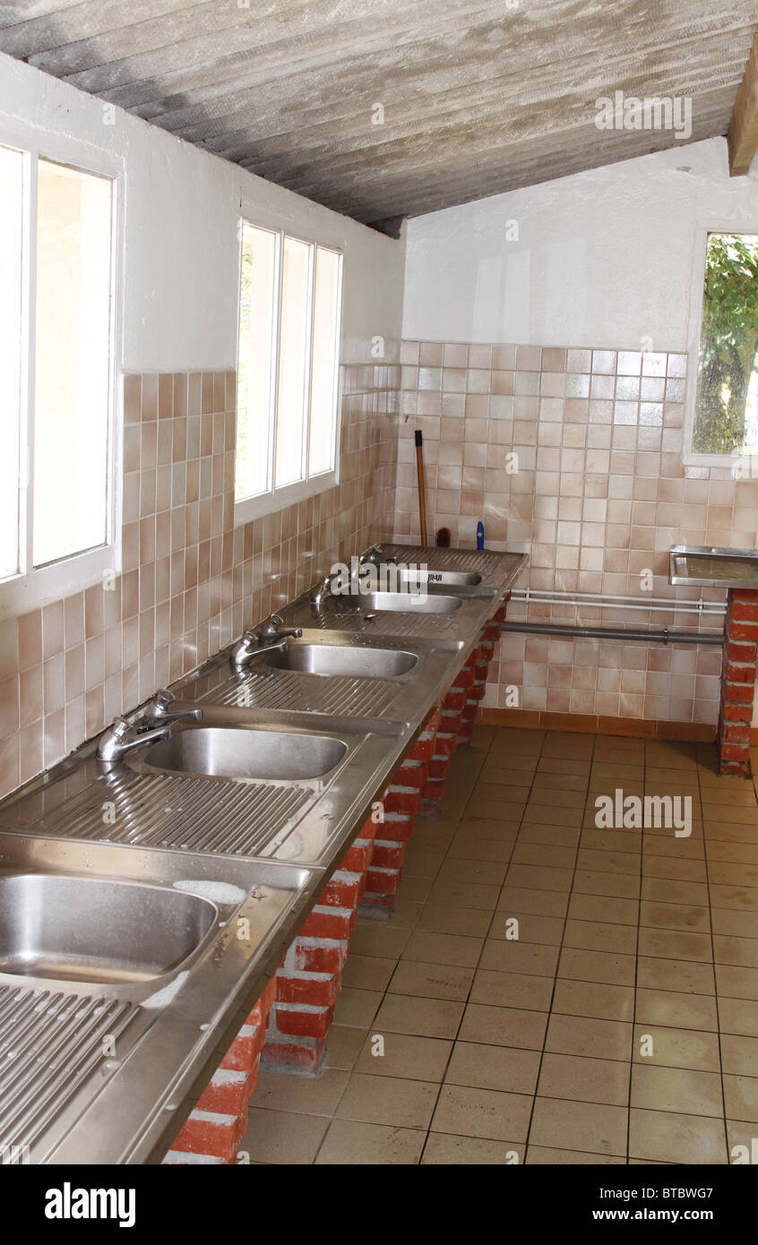 Row of caravan park or campsite stainless steel washing up sinks - Stock Image