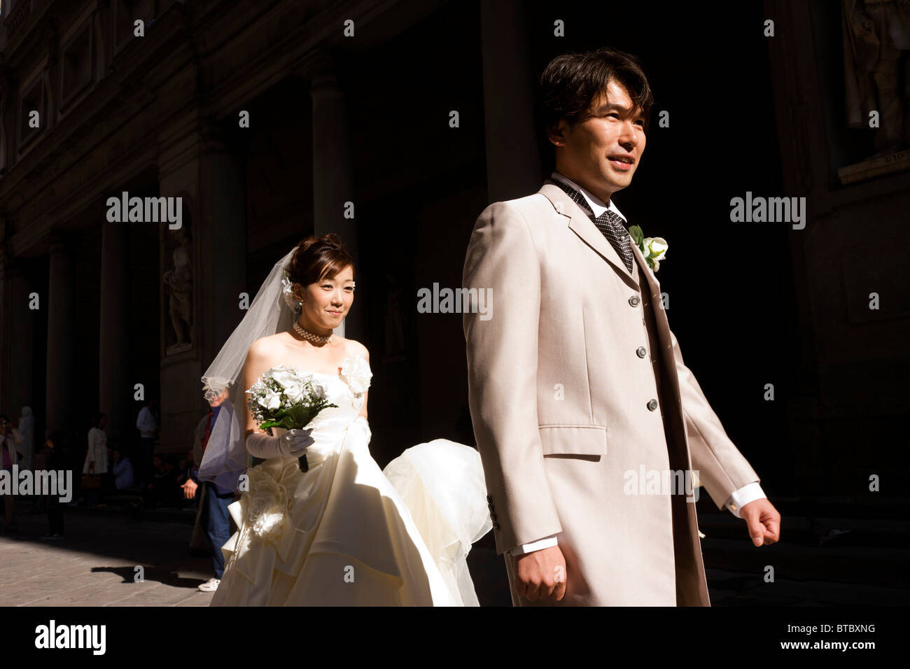 Chinese bride walks behind her new husband during photo shoot walk in Florence's Piazza degli Uffizi. - Stock Image