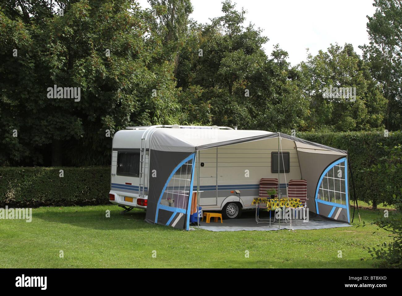 Touring caravan and awning on a pleasant woodland caravan park campsite. - Stock Image