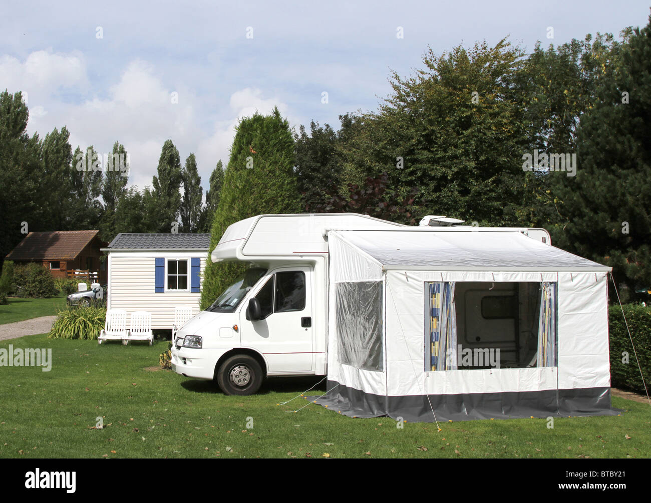 Motorhome with midi-size side awning on a woodland caravan park - Stock Image
